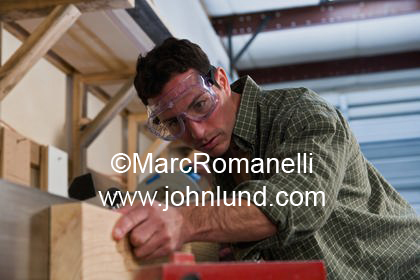 Business stock photo of a small business owner working on a wood project with power tools... maybe a table saw or planer.